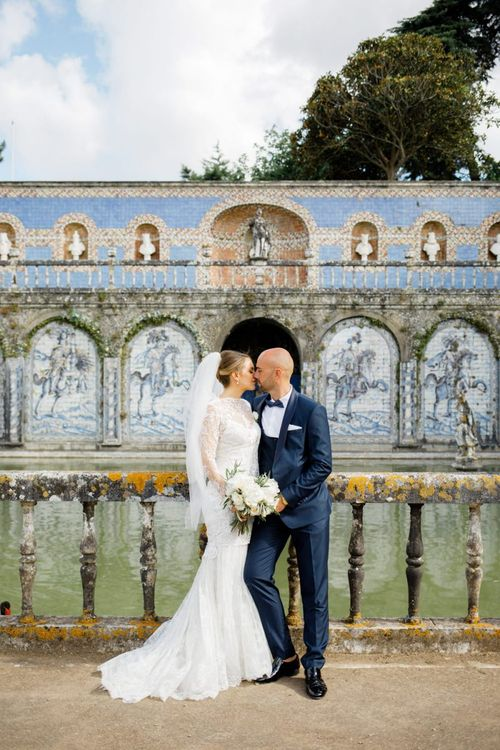 Bride in Lace Wedding Dress and Groom in Navy Blue Tuxedo