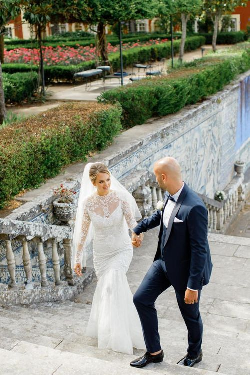 Groom in Navy Tuxedo Helping His Bride in a Long Sleeve Wedding Dress up the Steps
