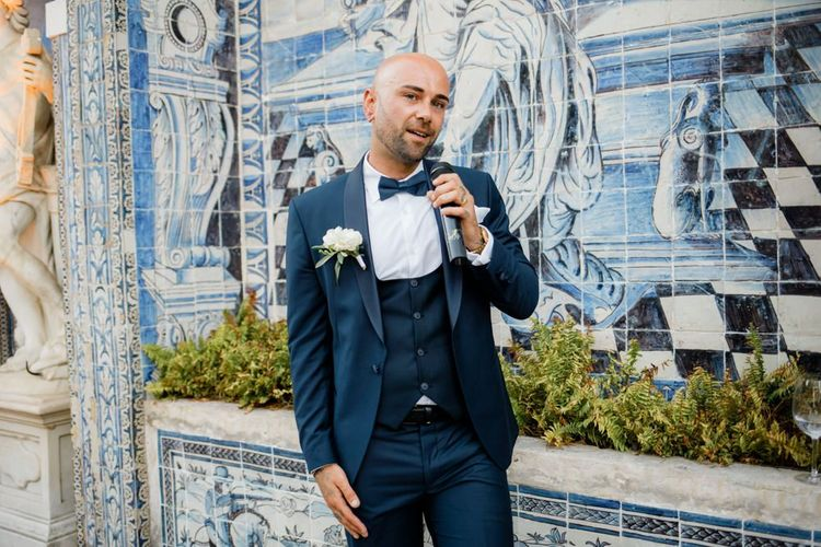 Groom in Navy Suit with Horseshoe Waistcoat and Bow Tie