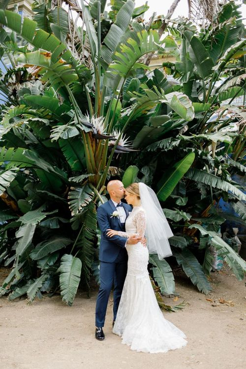 Bride in Yolan Cris Wedding Dress with Long Sleeves and Groom in Navy Suit