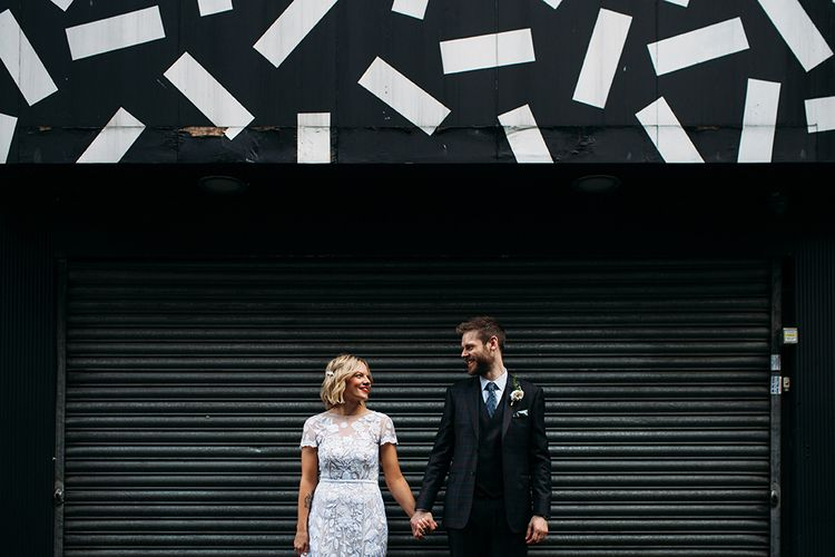 Bride in Lace Hermione De Paula Wedding Dress and Groom in Ted Baker Suit  Holding Hands