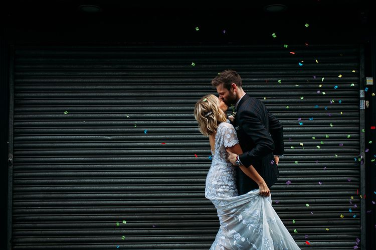 Bride in Lace Hermione De Paula Wedding Dress and Groom in Ted Baker Suit  Kissing with Confetti Bomb Going Off