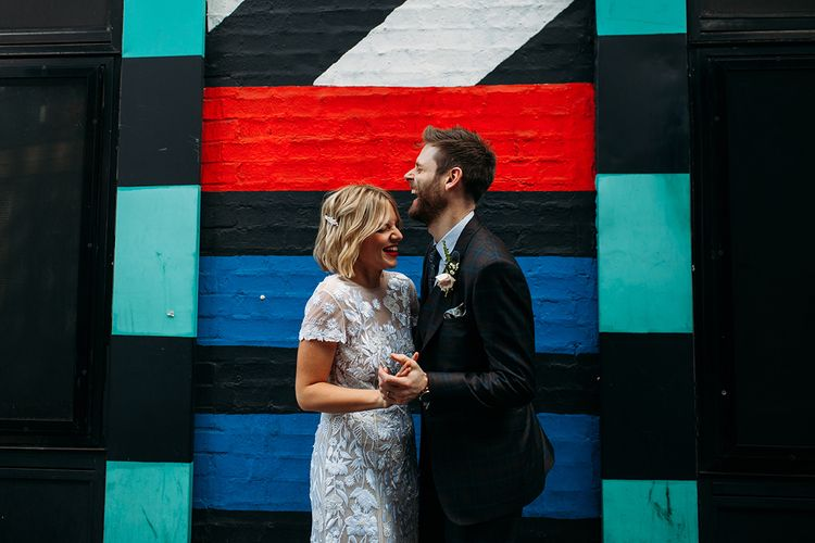 Bride in Lace Hermione De Paula Wedding Dress and Groom in Ted Baker Suit Standing in Front of Street Art
