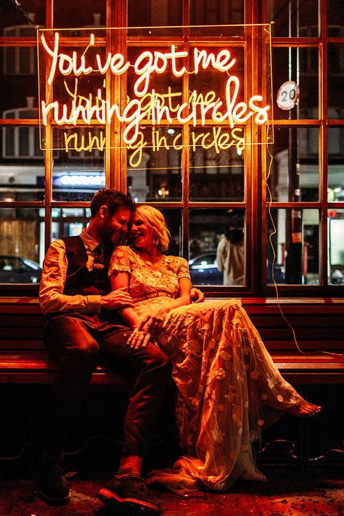 Bride in Lace Hermione De Paula Wedding Dress and Groom in Check Ted Baker Suit Sitting Under Bespoke Neon Sign by Bag and Bones
