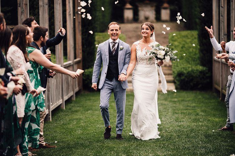 Confetti Moment | Bride in Pronovias Wedding Dress | Groom in Light Blue Suit Supply Suit | Stylish Tuscan Wedding at Vignamaggio Planned by The Wedding Boutique Italy | Samuel Docker Photography | Paul Vann Films