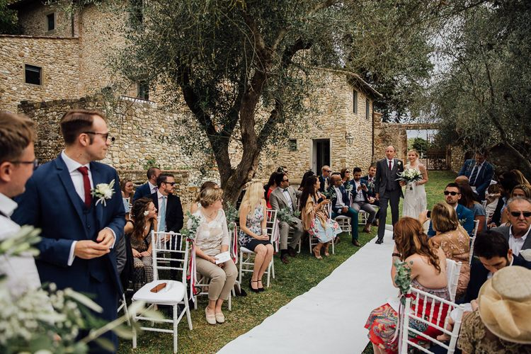 Outdoor ceremony in the Castle grounds. Destination wedding in Italy. Featuring RMW The List recommended suppliers Wiskow & White and Red on Blonde. Rue de Seine wedding gown with deep red chianti bridesmaid Rewritten dresses.