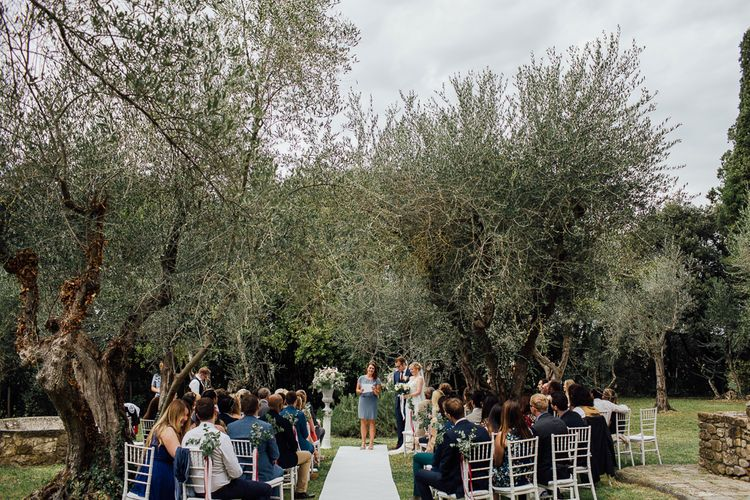 Ceremony in  Castle gardens. . Destination wedding in Italy. Featuring RMW The List recommended suppliers Wiskow & White and Red on Blonde. Rue de Seine wedding gown with deep red chianti bridesmaid Rewritten dresses.
