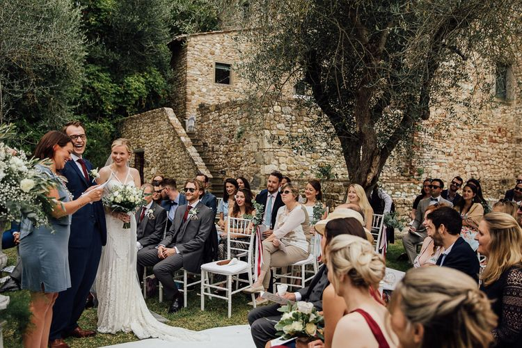 Ceremony in  Castle gardens. .Destination wedding in Italy. Featuring RMW The List recommended suppliers Wiskow & White and Red on Blonde. Rue de Seine wedding gown with deep red chianti bridesmaid Rewritten dresses.