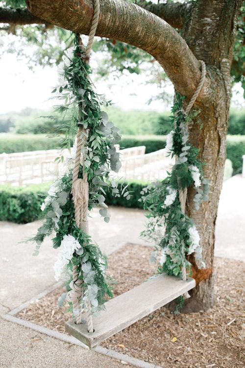 Swing at Froyle Park wedding covered in foliage and white flowers