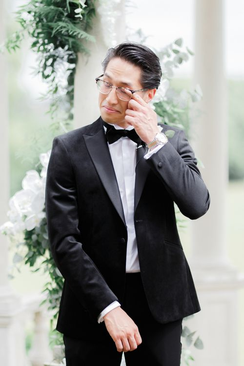 Emotional groom in black tuxedo at Froyle Park wedding ceremony