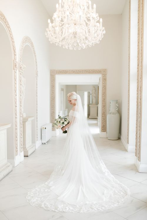 Bride in Mori Lee wedding dress and cathedral length veil standing in Froyle Park wedding venue