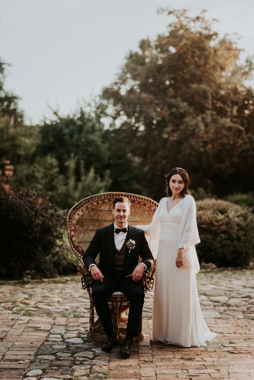Bride and groom on rattan chair