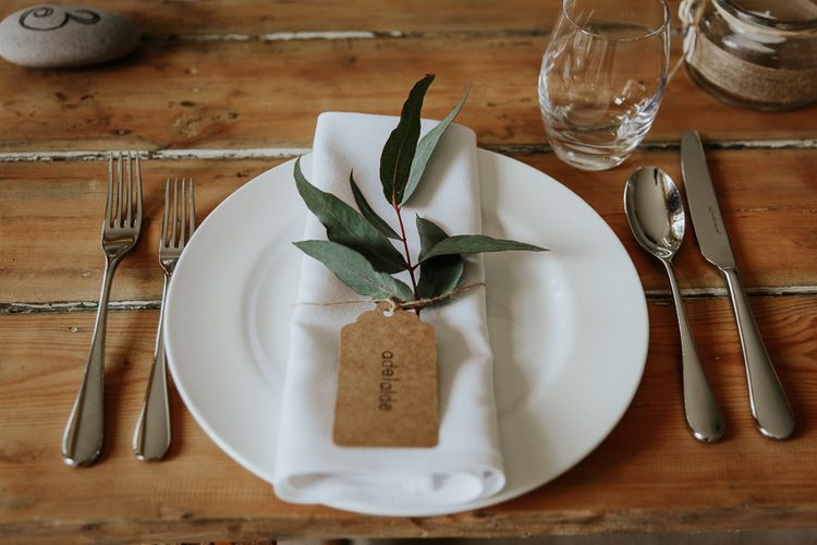 Elegant Place Setting with White Napkin, Craft Paper Luggage Tag and Single Foliage Stem
