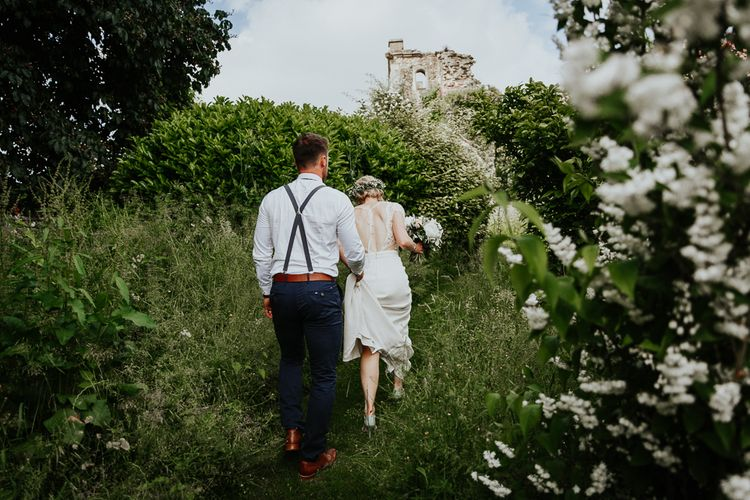 Groom Helping Bride in Handmade by Laura M Davey Wedding Dress with Low Back and Ribbon Detail Walk Through Euridge Manor's Gardens