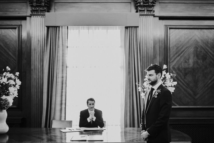 Wedding Ceremony at Old Marylebone Town Hall | Groom at the altar in Navy Ted Baker Suit | Navy & Silver Winter Wedding in London | Joasis Photography