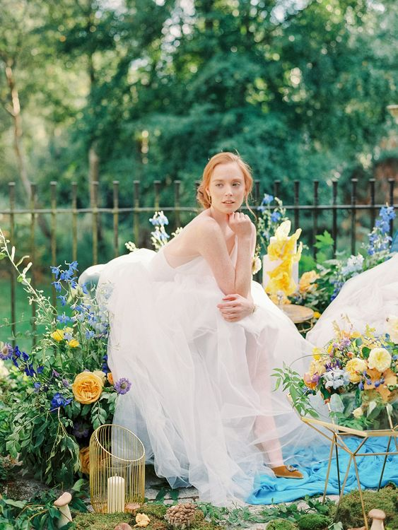 Beautiful Bride in Tulle Wedding Dress Surrounded by Yellow and Blue Wedding Flowers