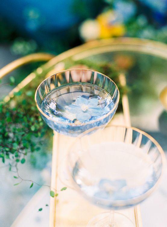 Blue Cocktails Served in Gold Rimmed Champagne Saucers
