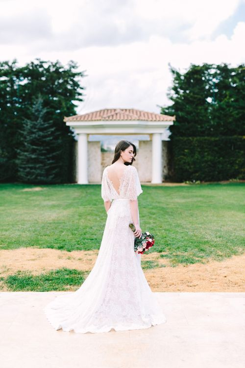 Bride in Lace Wedding Dress with Low Back Detail Holding a Red Wedding Bouquet
