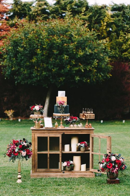 Wooden Dessert Table with Individual Cakes and Treats Surrounded by Floral Arrangement and Candles