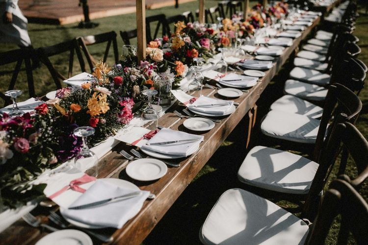 Bright pink and orange wedding flowers line the tables