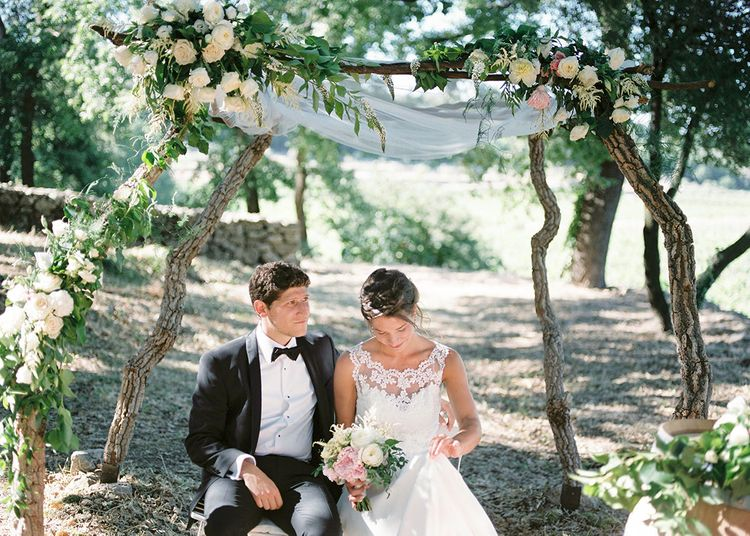 Floral Arch   Elegant Bride in Lace Wedding Dress   Groom in Black Tie Suit   Outdoor Wedding at Commanderie de Peyrassol, Provence, France Styled by La Chuchoteuse   Lace Bridal Gown   Black Tie Suit   Rustic Stretch Tent Reception   Raisa Zwart Photography