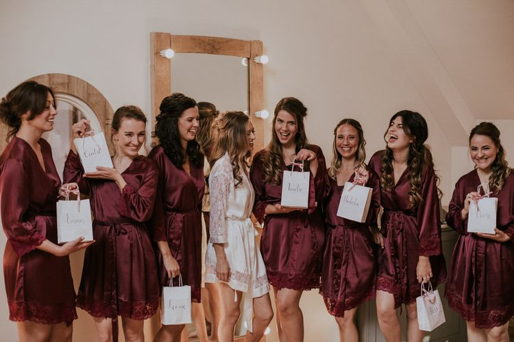 Bridesmaids in Matching Burgundy Robes with Bridesmaid Gift Bags | Millbridge Court, Surrey Wedding with DIY Decor, Foliage & Giant Balloons | Nataly J Photography