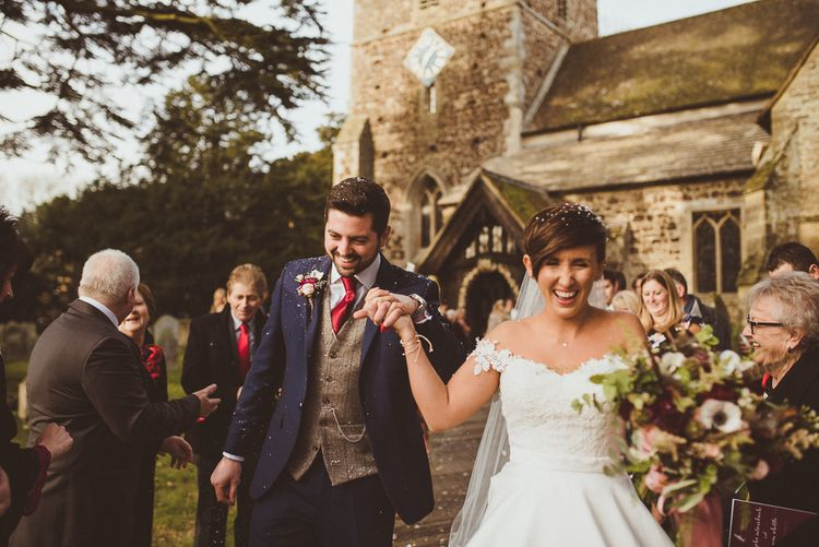 Church Confetti Moment | Bride in Lillian West Bridal Separates | Groom in Navy Suit & Tweed Waistcoat | Burgundy & Gold Winter Wedding at Ramster Hall Weddings, Surrey | Matt Penberthy Photography | John Harris Wedding Films