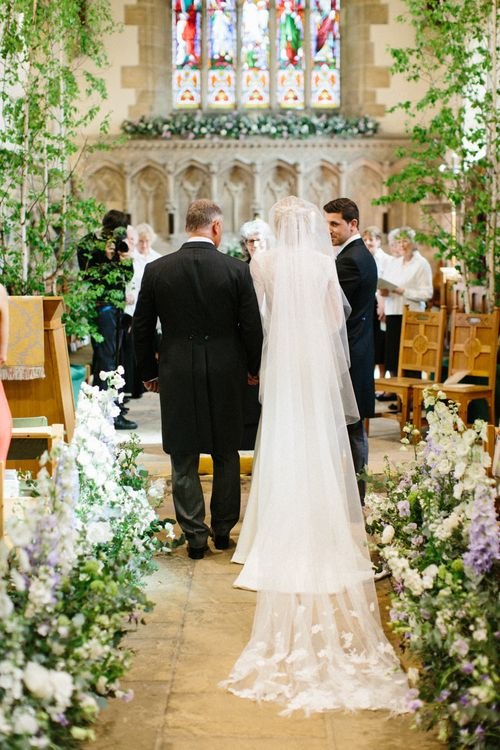 Lilac and white floral aisle runner | Silver Birch trees | Papakata Sperry Tent Wedding at family home | Sassi Holford Dress with added ivory Ostrich feathers to veil | Manolo Blahnik shoes | Images by Melissa Beattie