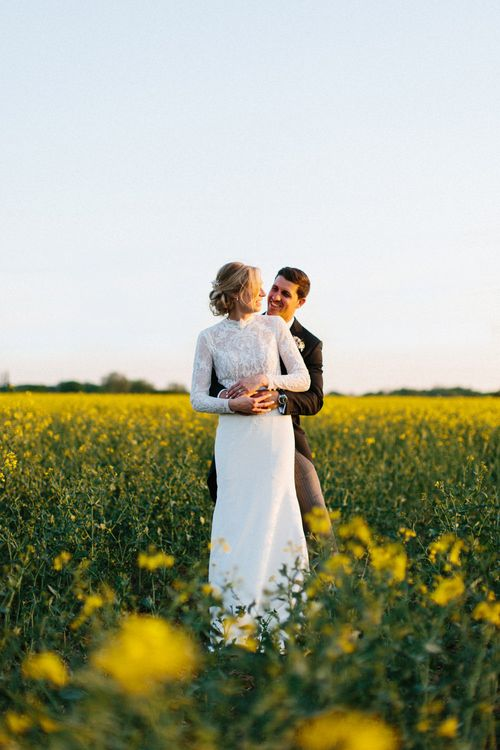 Yellow meadow couple shoot at dusk | Papakata Sperry Tent Wedding at family home | Sassi Holford Dress with added ivory Ostrich feathers to veil | Manolo Blahnik shoes | Images by Melissa Beattie