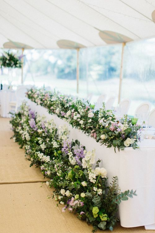 White, green and lilac flowers from the Church moved to reception to dress top table | Papakata Sperry Tent Wedding at family home | Sassi Holford Dress with added ivory Ostrich feathers to veil | Manolo Blahnik shoes | Images by Melissa Beattie