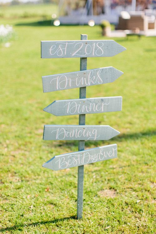 Wooden directional signage | Papakata Sperry Tent Wedding at family home | Sassi Holford Dress with added ivory Ostrich feathers to veil | Manolo Blahnik shoes | Images by Melissa Beattie