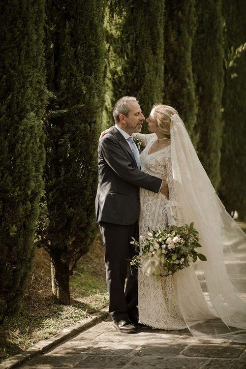 Bride in bell sleeve wedding dress with groom