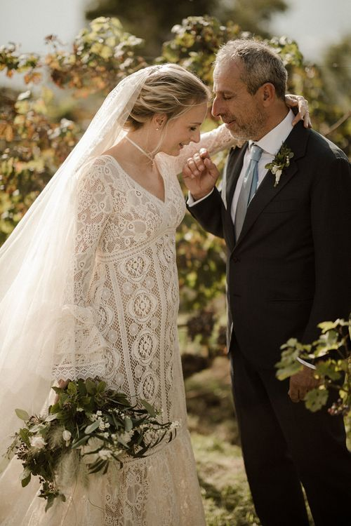 Bride in Bell sleeve wedding dress from Daphne Milano with groom