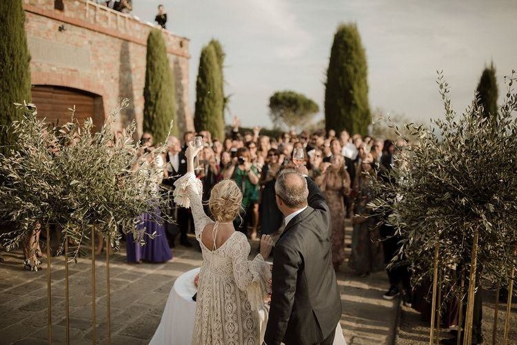 Bell sleeve wedding dress from Daphne Milano with groom toasting their wedding guests