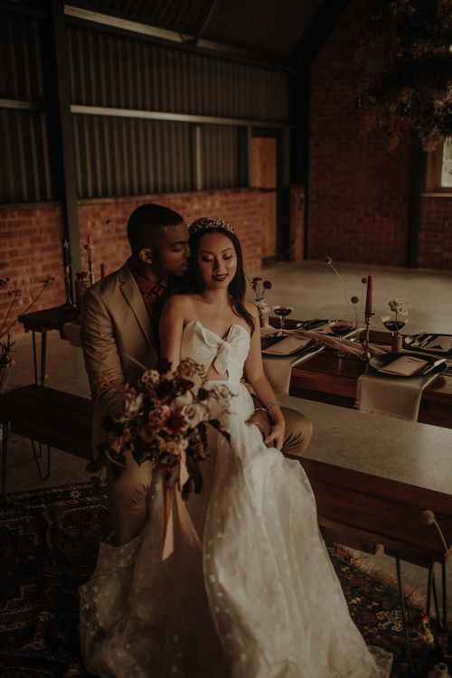Groom embracing his bride in a E&W Couture wedding dress