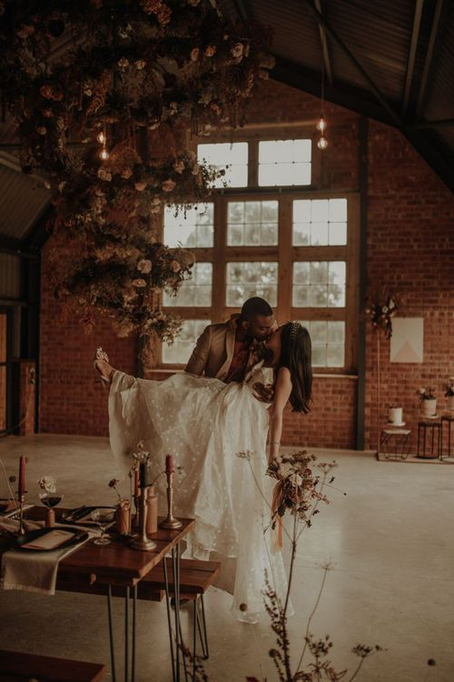 Groom picking up his bride in an embroidered E&W Couture wedding dress