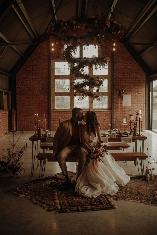 Intimate reception with rugs, candle light and spiral flower installation