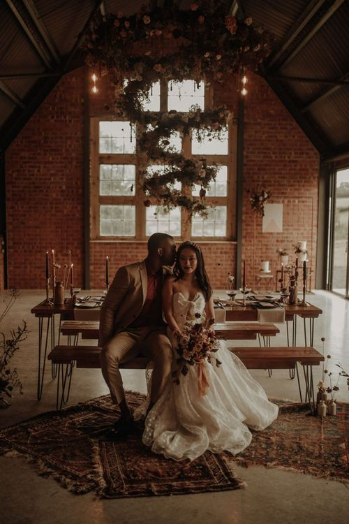 Bride and groom sitting at intimate wedding reception table at the Giraffe Shed