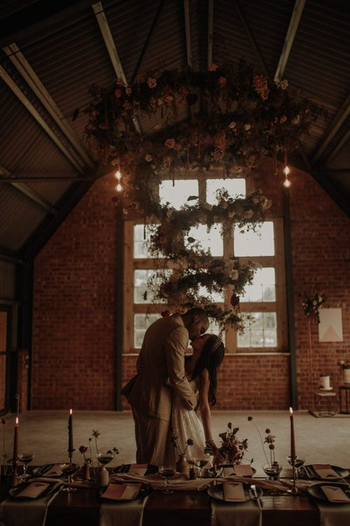 Bride and groom kissing under a floral spiral installation