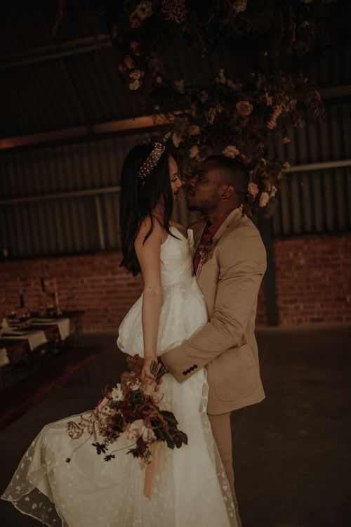 Groom in beige siut picking up his bride in a embroidered wedding dress