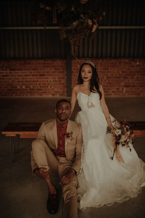 Portrait of groom in beige suit and burgundy shirt and bride in E&W Couture wedding dress at the Giraffe Shed