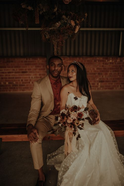 Portrait of groom in beige suit and burgundy shirt and bride in E&W Couture wedding dress by Esme Whiteside Photography