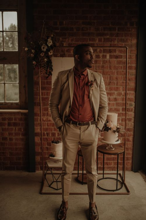 Stylish Black groom in beige suit and burgundy shirt  at the Giraffe Shed