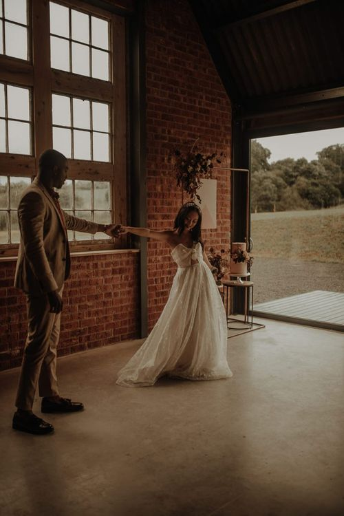 Black groom and Asian bride dancing at the Giraffe Shed