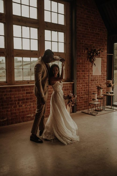 Bride in E&W Couture wedding dress being twirled by her groom