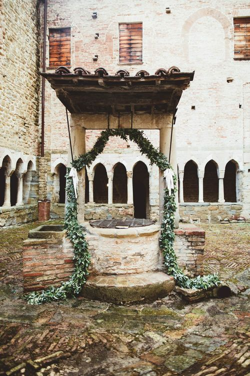 Ancient Well Decorated with Greenery Garland | Mint Green & White Outdoor Ceremony in a Abbazia Montelabate Monastery Cloister & Elegant Reception at Castello Ramazzao Castle, Italy | Maryanne Weddings Photography