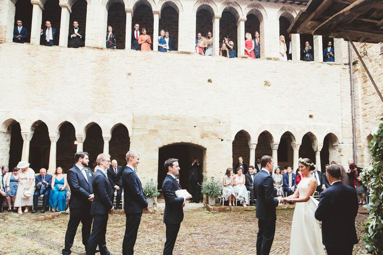 Wedding Ceremony Bride in Jesus Piero Wedding Dress from Morgan Davies Bridal | Groom in Black Suit | Mint Green & White Outdoor Ceremony in a Abbazia Montelabate Monastery Cloister & Elegant Reception at Castello Ramazzao Castle, Italy | Maryanne Weddings Photography