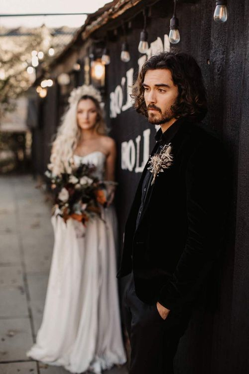 Groom in black shirt and velvet jacket for Halloween wedding