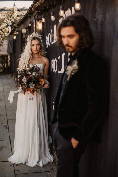 Bride in strapless wedding dress with autumn wedding bouquet for Halloween wedding