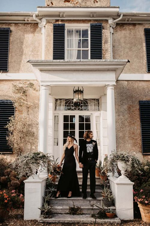 Stylish bride and groom in black wedding dress and t-shirt outside Preston Court